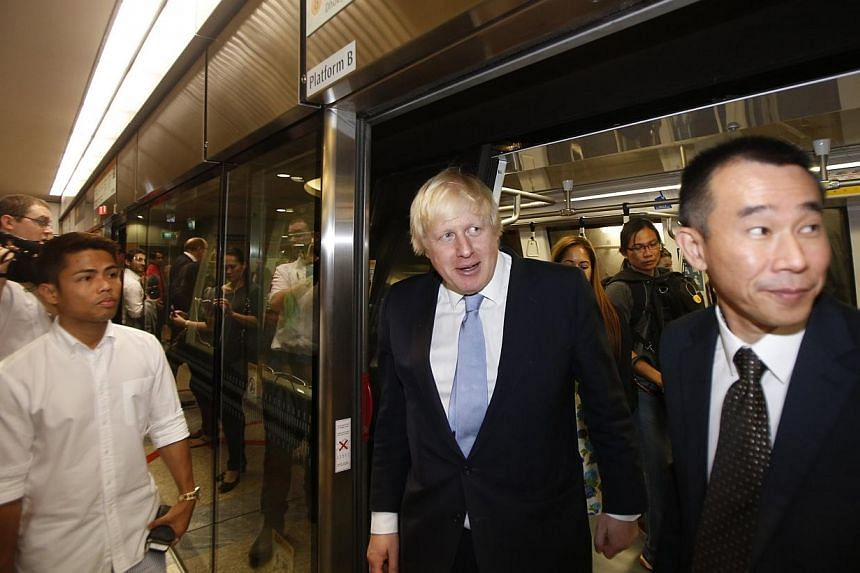 Mayor of London Boris Johnson disembarks the train with Managing Director of Singapore Mass Rapid Transit (SMRT) Trains Lee Ling Wee (right) at Marina Bay station during his visit in Singapore on Nov 28, 2014. -- PHOTO: REUTERS