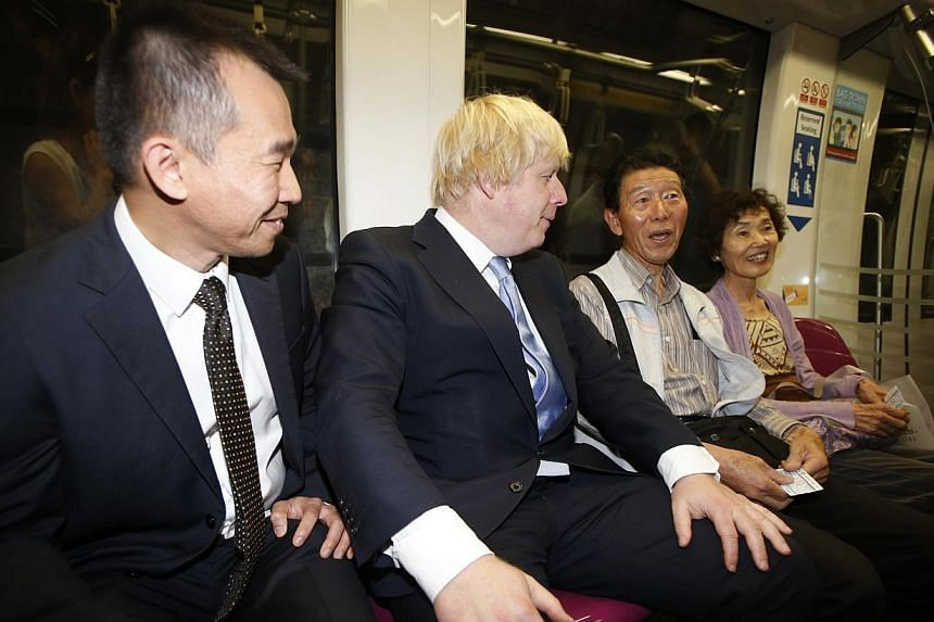 Mayor of London Boris Johnson (second left) introduces himself to two Japanese tourists on the train at Bayfront Mass Rapid Transit (MRT) station during his visit in Singapore on Nov 28, 2014. -- PHOTO: REUTERS