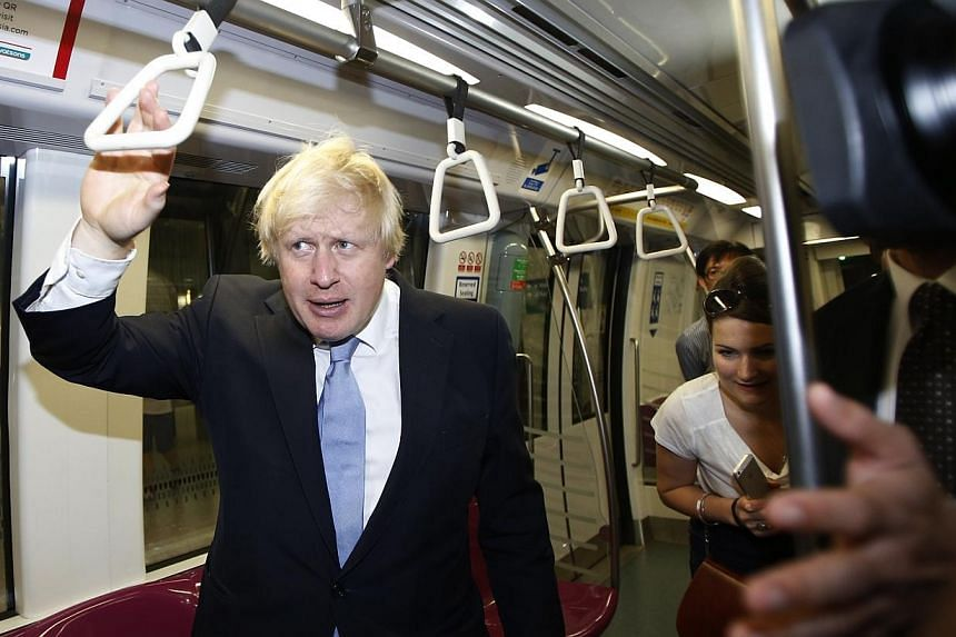 Mayor of London Boris Johnson finds a seat on the train at Bayfront Mass Rapid Transit (MRT) station during his visit in Singapore on Nov 28, 2014. -- PHOTO: REUTERS