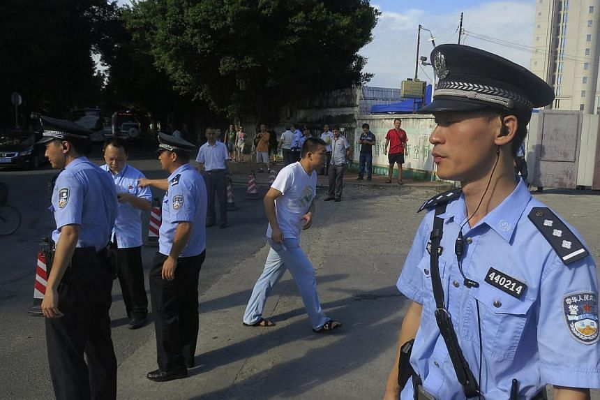 Police officers stand guard outside the court house, blocking roads to the Guangzhou People's Court in the southern Chinese city of Guangzhou on Sept 12, 2014.The long-awaited trial of a prominent Chinese writer and activist resumed in southe