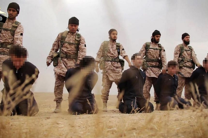 An image grab taken from a propaganda video released on Nov 16, 2014, by al-Furqan Media allegedly shows members of the Islamic State jihadist group preparing the simultaneous beheadings of at least 15 men described as Syrian military personnel.&nbsp