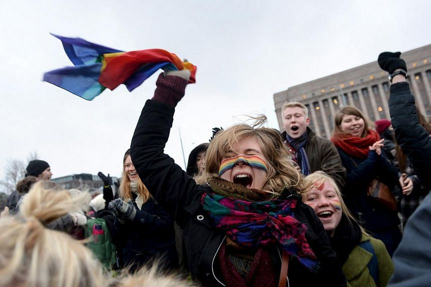 Supporters of same-sex marriage celebrate outside the Finnish Parliament in Helsinki on Nov 28, 2014.The Finnish Parliament on Friday narrowly approved a citizen's initiative to legalise same-sex marriage. -- PHOTO: REUTERS