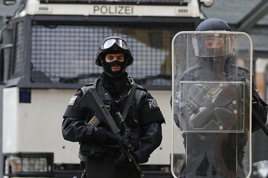 Austrian police officers in full combat adjustment for life threatening mission including gun (not used for riots in Austria) (left) and uniform of riot police officer (right) pose in front of a water cannon at their headquarters in Vienna on Oct 8,
