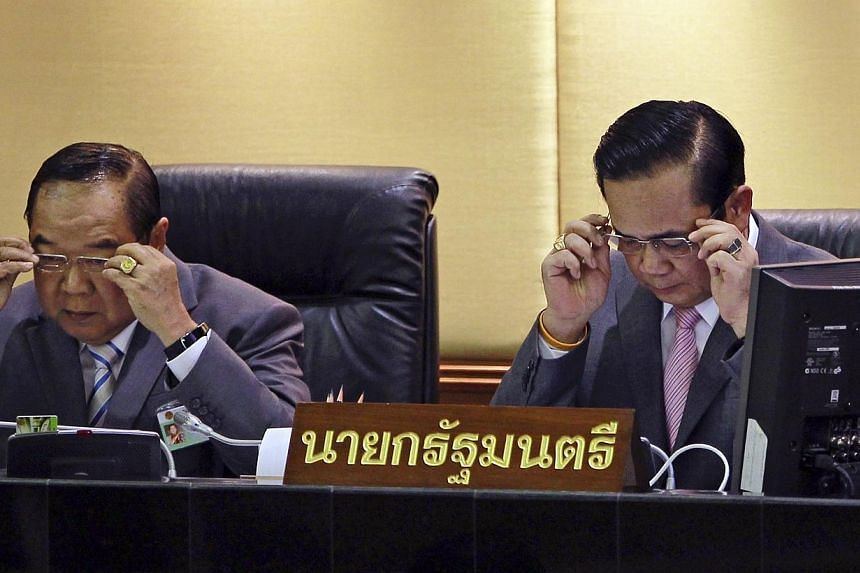 Thailand's Prime Minister Prayuth Chan-ocha (right) and Deputy Prime Minister and Defence Minister Prawit Wongsuwan don glasses before Prayuth reads out his government's policy, at the Parliament in Bangkok on Sept 12, 2014.Thailand's deputy pr