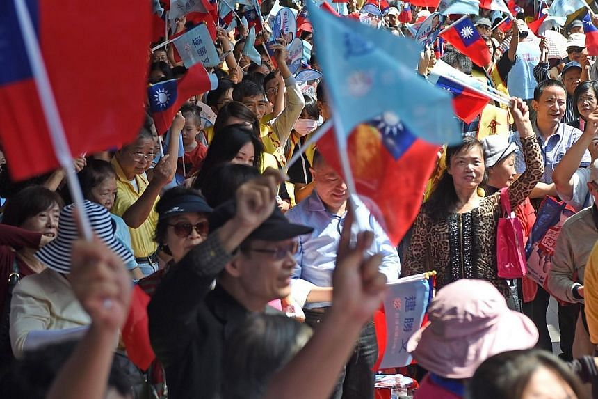 Supporters of Sean Lien, the Taipei mayor candidate from the ruling Kuomintang (KMT), waving flags during a campaign stop in Taipei on Oct 26, 2014.Taiwan goes to the polls on Saturday (Nov 29, 2014) to elect more than 11,000 public officials,
