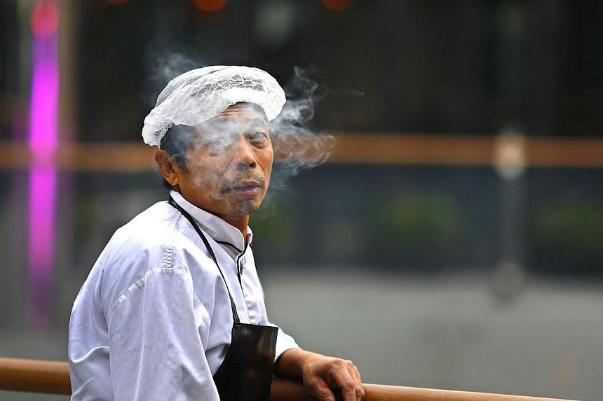 A man looks up as he smokes at Sanlitun Village, a shopping area in Beijing, Nov 23, 2014. China's capital on Friday passed a smoking ban for all indoor public places and offices, state media reported. -- PHOTO: REUTERS