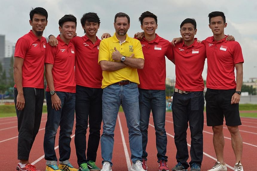The new Singapore Athletic Association head coach for sprints and hurdles, Mr Luis Cunha (centre), with the Singapore 4x100 team on Nov 28, 2014. -- ST PHOTO: CAROLINE CHIA