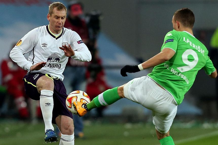 Everton's English defender Tony Hibbert (left) and Wolfsburg's Croatian midfielder Ivan Perisic vie for the ball during the UEFA Europa League Group H football match VfL Wolfsburg vs Everton FC in Wolfsburg, northern Germany on Nov 27, 2014. -- PHOTO