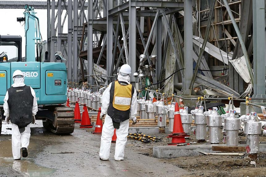 Workers wearing radiation protective gear stand outside of the No. 4 reactor building at Tepco's tsunami-crippled Fukushima Daiichi nuclear power plant in Fukushima prefecture on Nov 12, 2014. -- PHOTO: REUTERS