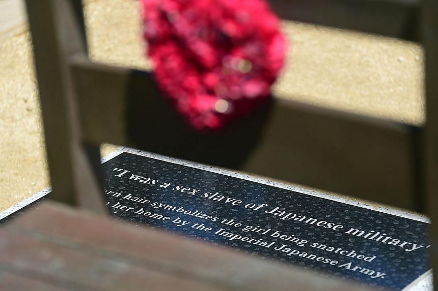 """Words on a plaque on the floor are seen throught the chair at the Comfort Women statue in Glendale, California on Sept 9, 2014.The English edition of The Japan News now uses the euphemism """"so-called comfort women"""", although the paper admits"""