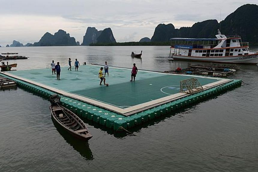 Youngsters playing football on a floating football pitch in Koh Panyee, in Thailand's southern Phang Nga province, on Oct 1, 2014. -- PHOTO: AFP