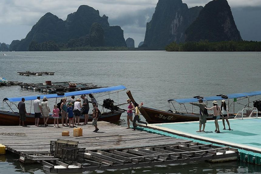 Tourists disembarking from long-tail boats as they arrive to Koh Panyee, in Thailand's southern Phang Nga province, on Oct 2, 2014. -- PHOTO: AFP