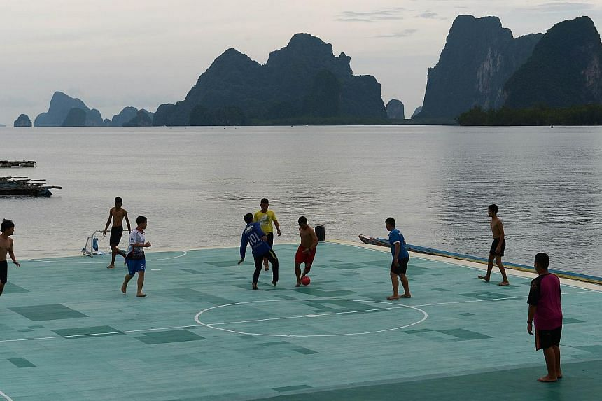 Youngsters playing football on a floating football pitch in Koh Panyee, in Thailand's southern Phang Nga province. -- PHOTO: AFP