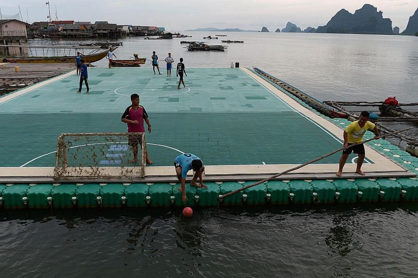 Youngsters recovering a football from the water as they play on a floating pitch in Koh Panyee, in Thailand's southern Phang Nga province. -- PHOTO: AFP