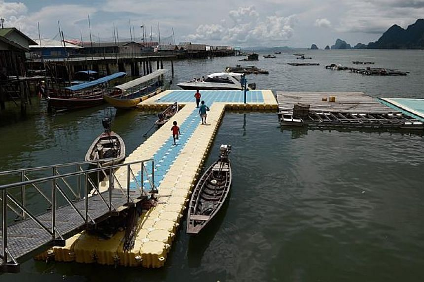 Children sell souvenirs to tourists disembarking from a speedboat as they arrive on Koh Panyee, in Thailand's southern Phang Nga province. -- PHOTO: AFP