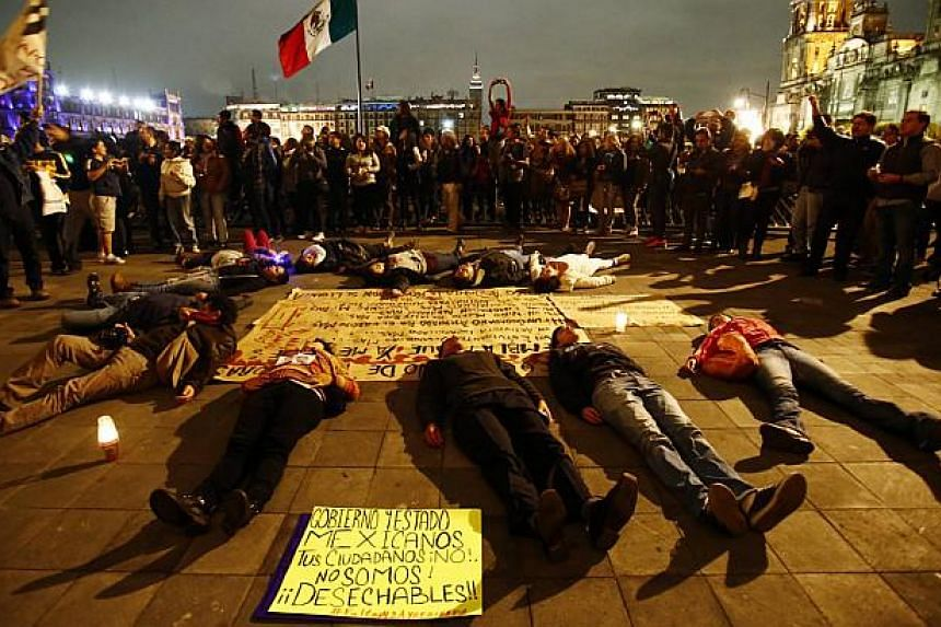 People lie in a circle pretending to be dead near the ceremonial palace of Mexican President Enrique Pena Nieto during a protest denouncing the apparent massacre of 43 trainee teachers in Mexico City late Nov 8, 2014. Eleven beheaded bodies were