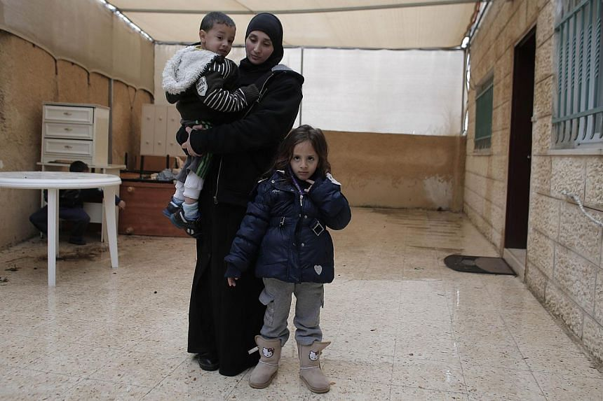 Nadia Abu Jamal (centre), Salma (right), four years old, and Mohamed, three years old, the widow and children of Ghassan Abu Jamal who carried out a deadly attack on a Jerusalem synagogue, stand in their house which has been ordered to be destroyed b