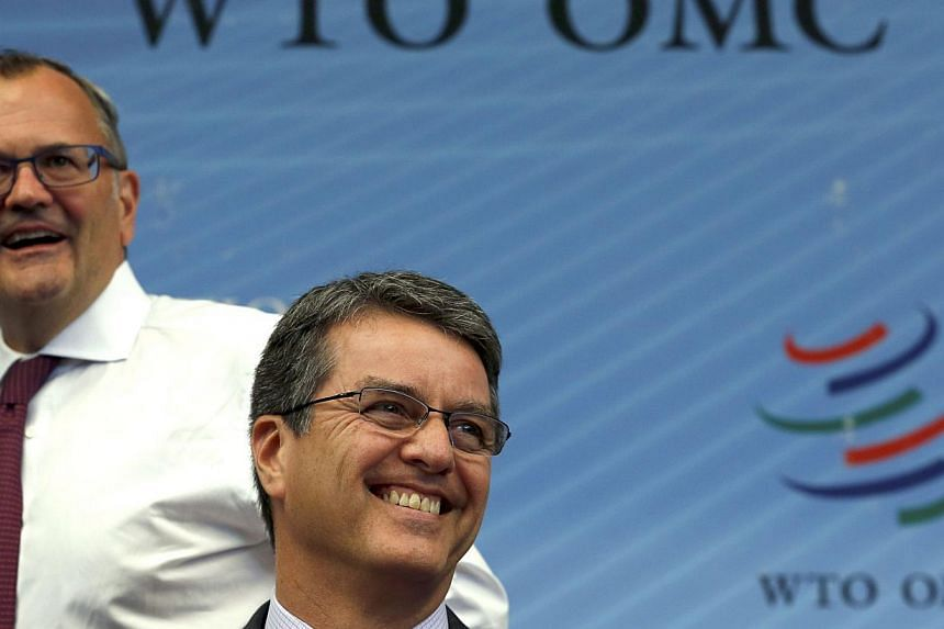 World Trade Organisation director-general Roberto Azevedo (right) smiles next to spokesman Keith Rockwell at the WTO meeting in Geneva Nov 27, 2014. The World Trade Organisation adopted the first worldwide trade reform in its history on Thursday, aft