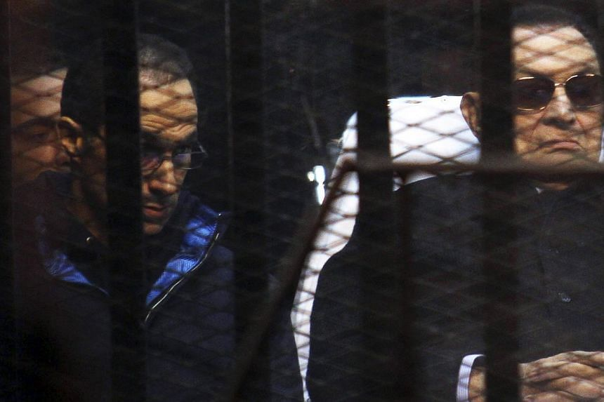 "Former Egyptian President Hosni Mubarak listens next to his son Gamal (left) inside a dock during his trial at the police academy on the outskirts of Cairo on Nov 29, 2014. Mubarak said Saturday he ""did nothing wrong"", after a court dismissed a murde"