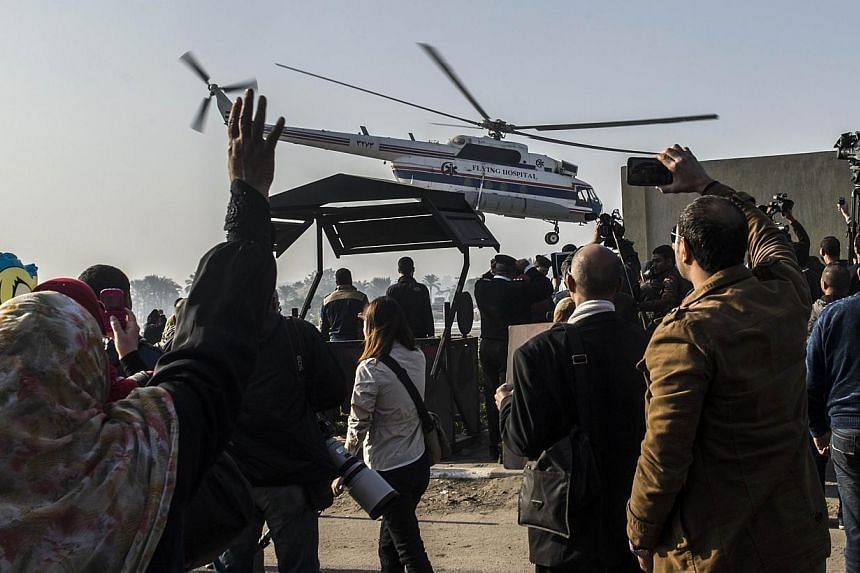 An Egyptian supporter of former president Hosni Mubarak waves as the helicopter carrying the former leader leaves the Maadi military hospital en route to the court in Cairo for his trial on Nov 29, 2014.An Egyptian court on Saturday acqui