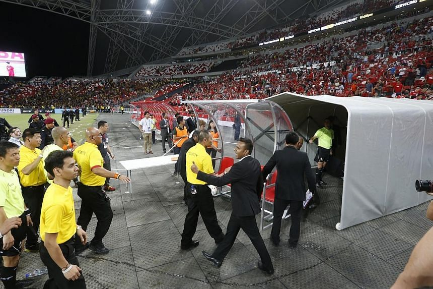 Referees leaving the field at the AFF Suzuki Cup's Singapore v Malaysia match at the National Stadium on Nov 29, 2014. -- ST PHOTO: KEVIN LIM