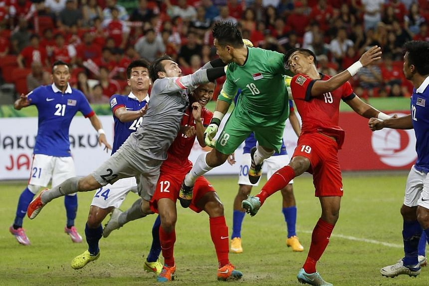 Singapore's goalkeeper Hassan Sunny (in green) heads against his Malaysian counterpart as Singapore tries to salvage a draw in the AFF Suzuki Cup at the National Stadium on Nov 29, 2014. -- ST PHOTO: KEVIN LIM