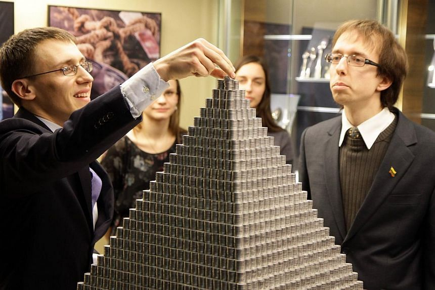 A man puts finishing touches to a pyramid made of 1,000,935 Lithuanian cents on Nov 29, 2014 in Vilnius, Lithuania.The Baltic nation of Lithuania on Saturday unveiled what it billed as the world's largest-ever coin pyramid ahead of its switch f