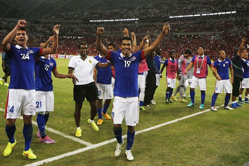 Malaysia acknowledges fans after defeating Singapore in their Suzuki Cup Group B match at the National Stadium in Singapore on Nov 29, 2014. -- PHOTO: REUTERS