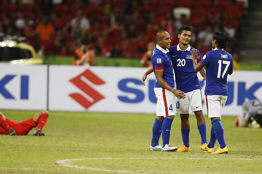 Malaysia's (from left) Mahalli Bin Jasuli, Mohd Hafiz Bin Kamal and Mohd Amri Bin Yahyah celebrate defeating Singapore in their Suzuki Cup Group B match at the National Stadium in Singapore on Nov 29, 2014. -- PHOTO: REUTERS