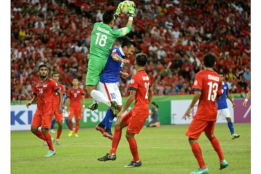 Singapore's goalkeeper Hassan Sunny (in green) saves the ball from Malaysia's Safee Sali (in blue) during their AFF Suzuki 2014 Cup football match at the National stadium in Singapore on Nov 29, 2014. -- PHOTO: AFP