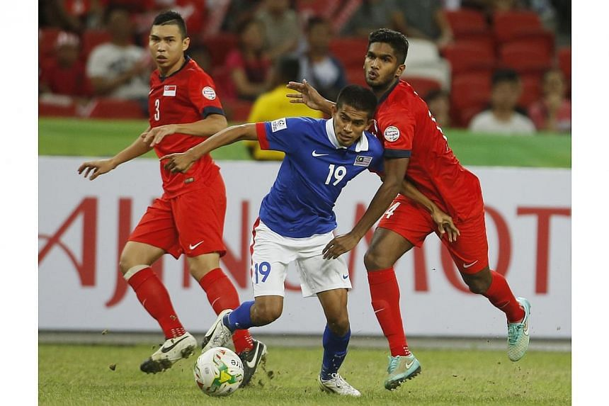 Malaysia's Azammuddin Bin Mohd Akil (centre) is challenged by Singapore's Harris Harun (right) during their Suzuki Cup Group B match at the National Stadium in Singapore on Nov 29, 2014. -- PHOTO: REUTERS