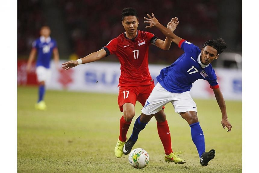 Malaysia's Mohd Amri Bin Yahyah challenges Singapore's Mohammad Shahril Bin Ishak (left) during their Suzuki Cup Group B match at the National Stadium in Singapore on Nov 29, 2014. -- PHOTO: REUTERS