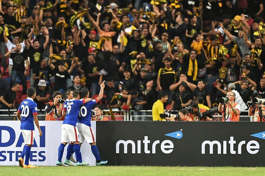 Malaysia players (in blue) celebrate after scoring their first goal against Singapore during their AFF Suzuki 2014 Cup football match at the National Stadium in Singapore on Nov 29, 2014. -- PHOTO: AFP