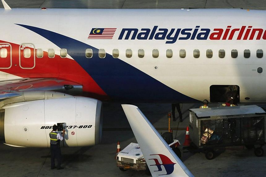 A ground crew member works on a Malaysia Airlines Boeing 737-800 airplane on the runway at Kuala Lumpur International Airport in Sepang on July 25, 2014.Striken Malaysia Airlines apologised on Saturday for a year-end promotion tweet that draw a