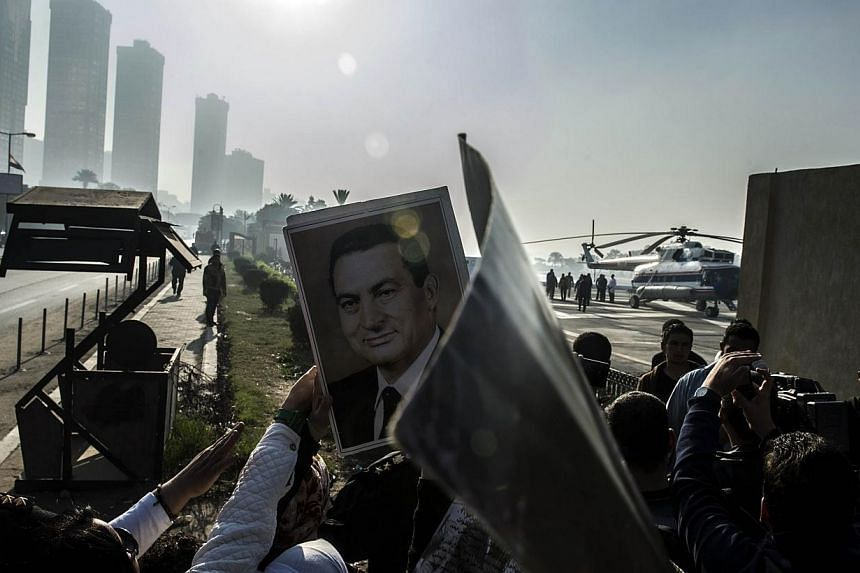 An Egyptian supporter of Egypt's former president Hosni Mubarak holds his portrait as a medical helicopter takes off outside Maadi military hospital transporting the deposed leader to the court in Cairo for his trial on Nov 29, 2014. -- PHOTO: AFP