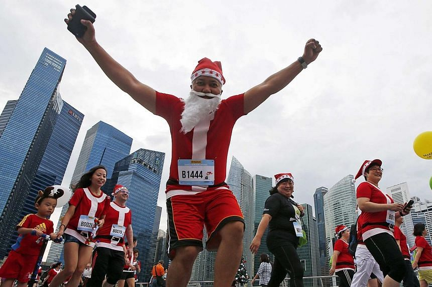 A participant reacts to the camera as they start the Santa Run for Wishes charity run along the Marina Promenade in Singapore's central business district on Nov 29, 2014. Singapore's first Santa-themed run saw some 4,600 runners take to the Mari