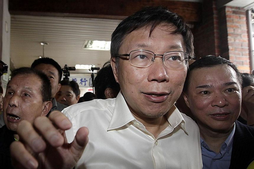 Taipei mayoral candidate Ko Wen-je greets supporters during an electoral campaign visit to a market ahead of local elections in Taipei on Nov 28, 2014.An independent candidate backed by Taiwan's opposition, pro-independence party on Saturday cl