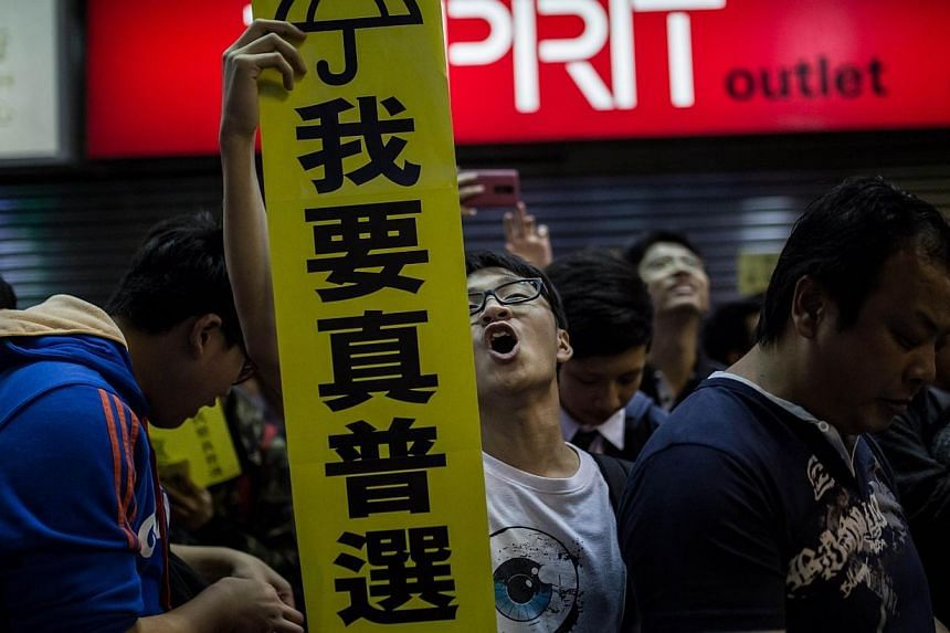 A pro-democracy protester (centre) holds a sign for the Umbrella Movement as he shouts slogans in the Mongkok district of Hong Kong on November 28, 2014.Hong Kong's leader admitted on Saturday that the frustration among young people over a lack