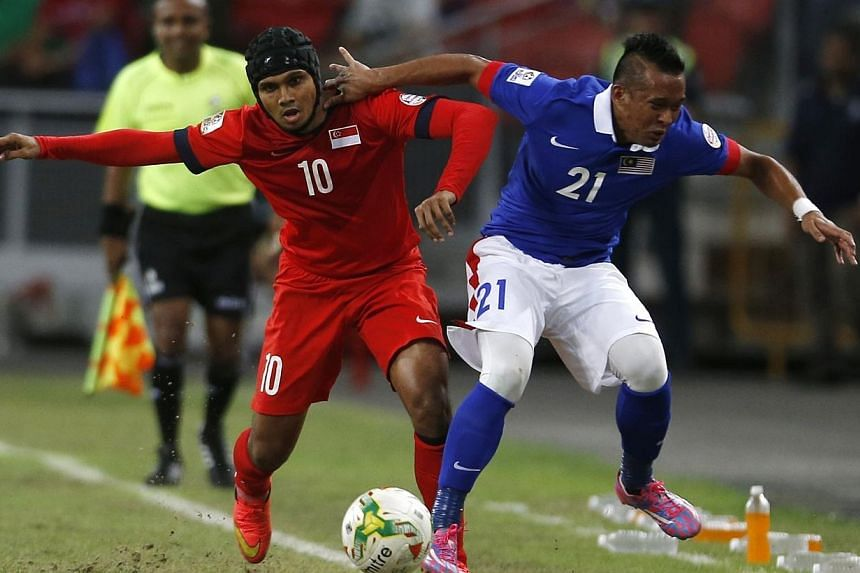 Malaysia's Muhammad Zubir Bin Mohd Azmi (right) challenges Singapore's Fazrul Nawaz Shaul Hameed during their Suzuki Cup Group B match at the National Stadium in Singapore Nov 29, 2014. -- PHOTO: REUTERS
