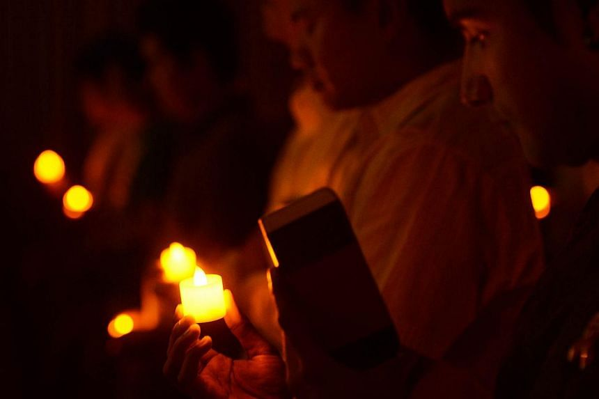 People holding electric candles at the National Skin Centre Auditorium in memory of those who died from HIV and Aids during the 30th anniversary of the International Aids Candlelight Memorial, organised by Action for Aids Singapore in May 2013. -- PH