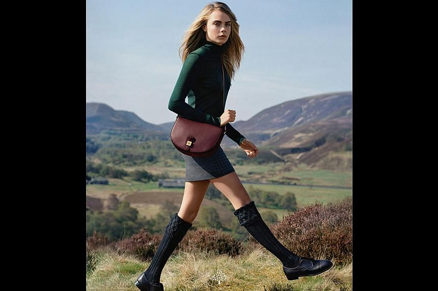 Model Cara Delevingne carries Mulberry's Tessie satchel, which was launched in May and is one of the brand's more affordable offerings. -- PHOTO: MULBERRY