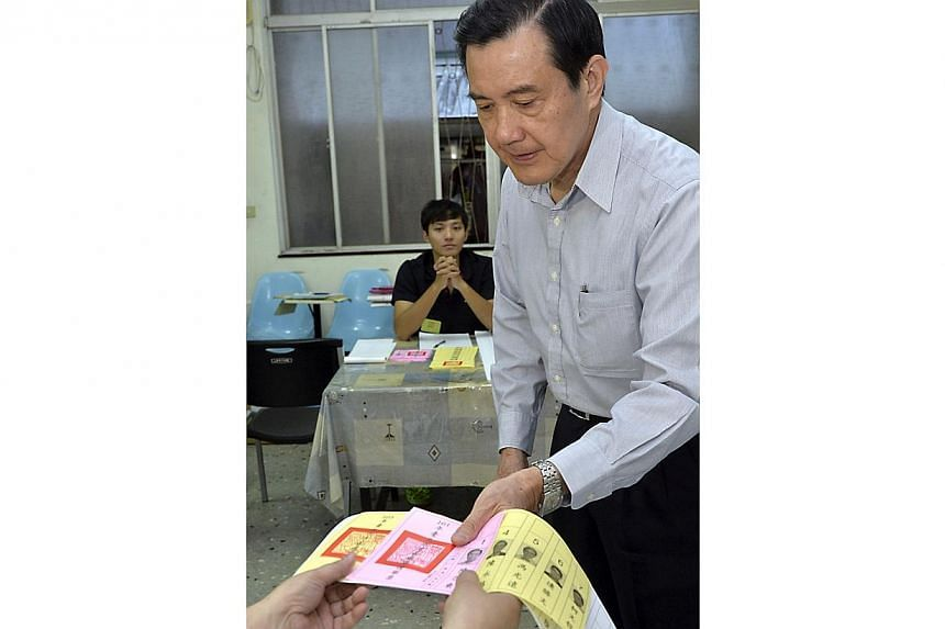 Taiwan's President Ma Ying-jeou receives a ballot at a voting station during local elections in Taipei on Nov 29, 2014. -- PHOTO: REUTERS
