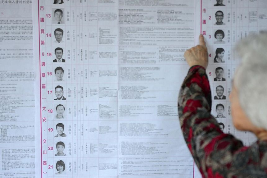 A local resident checks a list of candidates before voting at a polling station in Taipei on Nov 29, 2014. -- PHOTO: AFP