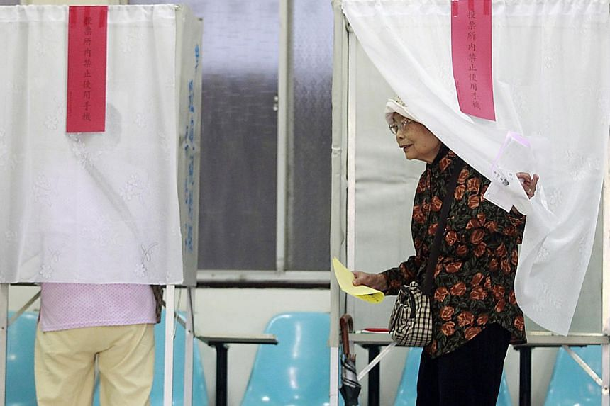 A woman walks out of a voting booth at a polling station during local elections in Taipei on Nov 29, 2014. -- PHOTO: REUTERS