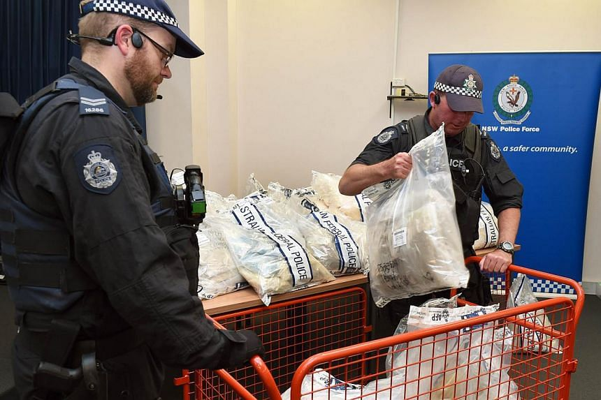 Australian police officers handling some of the seized drugs in one of the largest drug busts in the country's history, worth up to S$1.66 billion, in Sydney on Nov 29, 2014. -- PHOTO: AFP