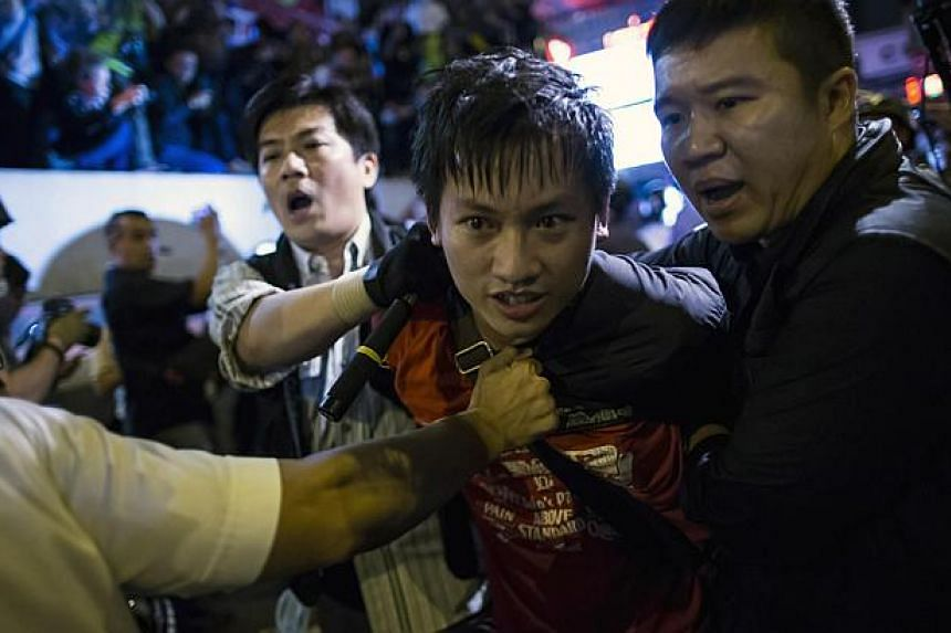 A pro-democracy protester is detained by police during a confrontation at Mongkok shopping district in Hong Kong early Nov 29, 2014. Thousands of pro-democracy activists clashed with police in running scuffles in the gritty district of Mongkok e