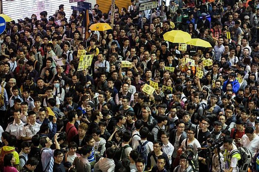 """Pro-democracy protesters shout slogans as they gather in a street in the Mongkok district of Hong Kong on Nov 28, 2014. Amnesty International on Nov 28 warned Hong Kong police against """"excessive force"""" ahead of a planned rally by pro-democracy demons"""