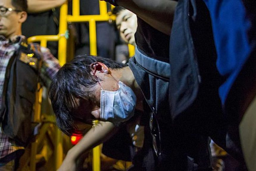 A pro-democracy protester is detained by police during a confrontation at Mongkok shopping district in Hong Kong early Nov 29, 2014. -- PHOTO: REUTERS