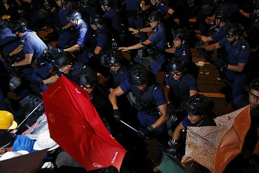 Riot police disperse pro-democracy protesters carrying umbrellas during a confrontation at Mongkok shopping district in Hong Kong early Nov 29, 2014. -- PHOTO: REUTERS