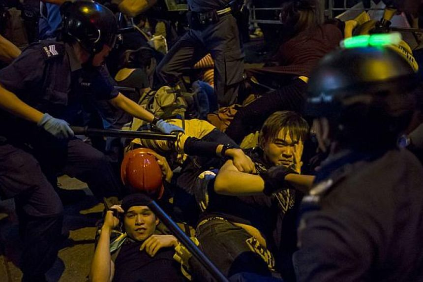 Pro-democracy protesters fall on the ground as they are chased by riot police at Mong Kok shopping district in Hong Kong early Nov 29, 2014. -- PHOTO: REUTERS